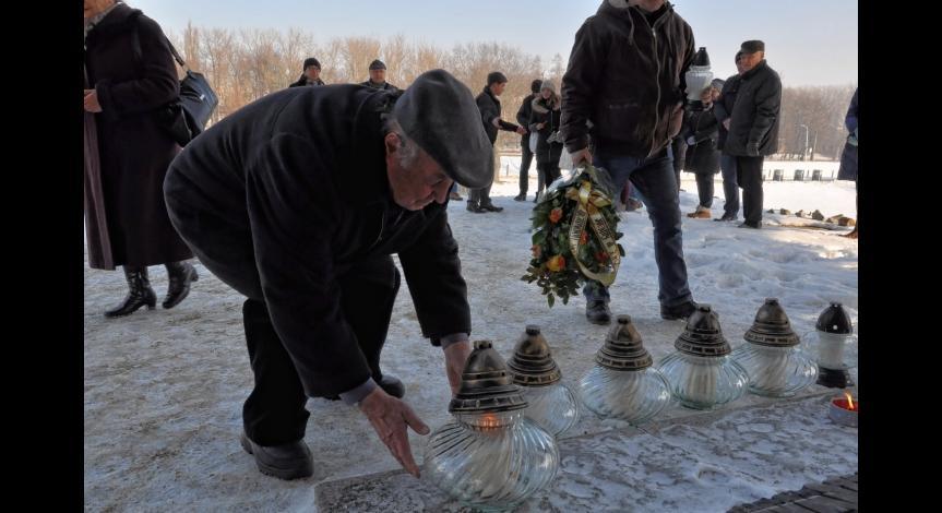 Powiększ obraz: Uczestnicy Międzynarodowego Dnia Pamięci o Ofiarach Holokaustu zapalają znicze przy Pomniku-Bramie